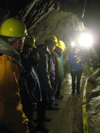Photo of people underground wearing yellow hard hats.