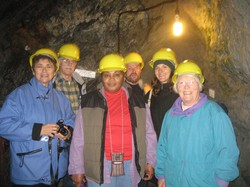 Photo of six people wearing yellow hard hats with a mine wall behind them.