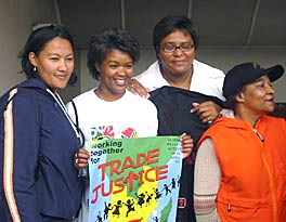 "Photograph of four women. One displays a sign that says ""Working together for trade justice."""