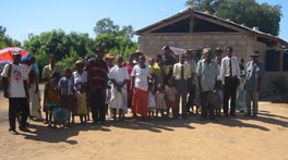 Photo of about thirty people lined up on the dirt in front of a small structure, perhaps a church.