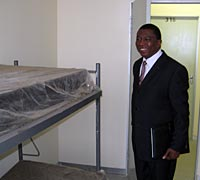 Photo of a man wearing a suit and tie standing in a hospital room next to a bunk bed. The mattresses of the bed are covered in clear plastic.
