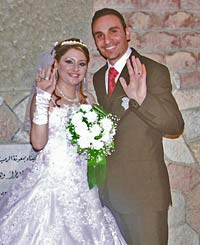 Photo of a couple at their wedding waving at the camera. The bride holds a bouquet of white flowers.
