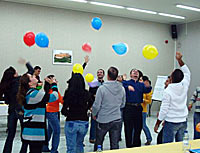 Photo of people in a room batting balloons into the air. Everyone is looking up at the balloons. Many have their arms cocked and ready to swing.