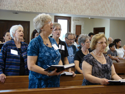 A group of women and men singing in worship.