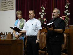 Nuhad Tomeh, right, singing in worship with a woman and a man to his right.