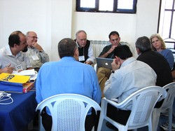 Photo of seven men and a woman seated in a circle; one man has an open laptop.