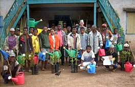 Photo of a group of people holding watering cans; in front of them is a line of trees in pots.