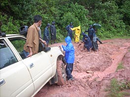 Photo of many people working to maneuver a car through a mud track