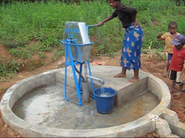 A group of kids near a newly installed water pump.