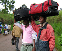 Photo of two men carrying suitcases on their heads.