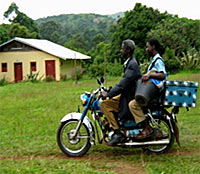 Photo of two people on a motorcycle. A man in a jacket rides in front. A young woman holding a bucket sits behind him. Behind the young woman is a bright blue trunk tied on the very back of the motorcycle.