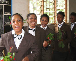 Photograph of five young women holding flowers. They are all dressed in brown jackets, white blouses and black-and-white bow ties. They appear to be singing and moving forward.