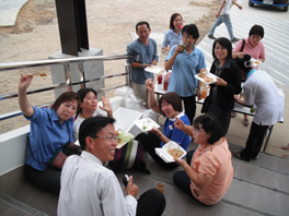 A group of people holding styrofoam containers of food and sitting on step outdoors.