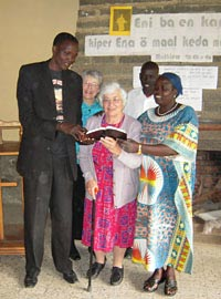 Photo of several people reading from a Bible.