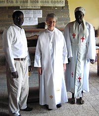 Photo of Carolyn in white clerical garb, flanked by a man on her right and a woman also in clerical robes.