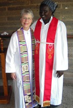 Photo of Carolyn standing next to a woman; both wear clerical robes and stoles.