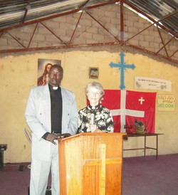 Carolyn Weber standing next to a man wearing a clerical collar behind a lecturn.
