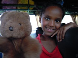 Photo of a child and a bear puppet; it has light brown fur, black eyes and a black nose.