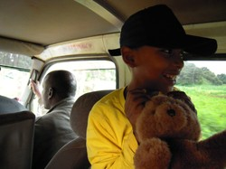 Photo of a child holding a fuzzy bear and sitting in a vehicle.
