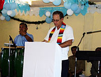 Photo of Don at a pulpit wearing a white shirt and a brightly colored stol.
