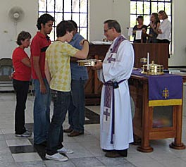 Photo of a man wearing clerical garb giving Communion elements to a young man.
