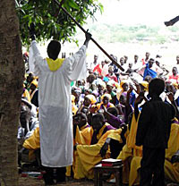 Photo of a worship service outdoors. A man stands in a white robe holding a staff high while a large group of people are seated on the ground in front of them. Many of them wear saffron-colored robes.