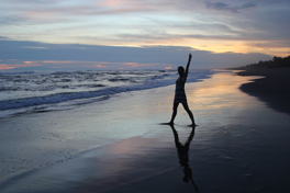 A woman lifting her hand on a beach during sunset.