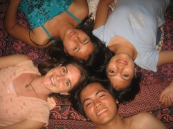 Photo of four young people lying on the floor with their heads together and looking up at the camera.