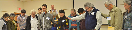 Teaching Elder Chester Topple (center left) leads the presbytery in prayer for Claudia Aguilar (center right) following her successful examination for ordination.