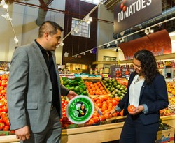 Gerardo Reyes Chavez of CIW (left) and Felis Andrade of Giant Food place a Fair Food sign next to tomatoes in Giant's O Street store in Washington DC.