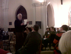 Peter Block speaking to an audience in a church.