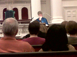 The Rev. Dr. Susan Andrews speaking from a lectern to an audience in a church.