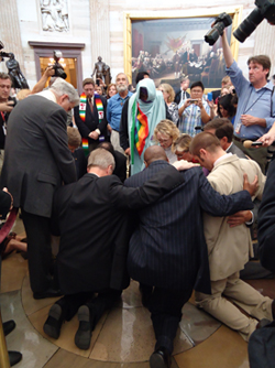 A group of religious leaders kneeling and prayer in the Capitol Hill Rotunda in Washington, D.C.