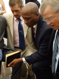 The Rev. Dr. J. Herbert Nelson praying with a group of religious leaders during a protest at the Capitol Hill Rotunda.