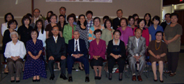 A large group of people in a room, sitting and standing together for a group photo.