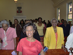 A large group of women standing at the pews in a church. A Presbyterian symbol is behind them.