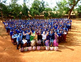 Teachers and mission workers with a large group of schoolchildren in blue uniforms, together for a photo outside of their school.