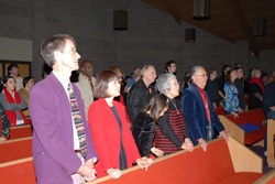 People standing behind pews in worship.