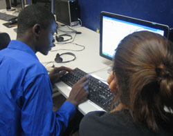 A young man typing on a computer beside a young woman.