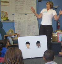 A woman, standing with a surprised look in a classroom with students.