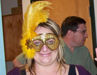 A woman wearing a gold, glittery mask and a bright yellow feather.