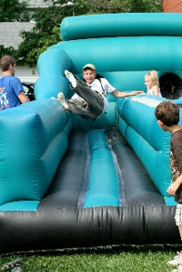 Kids enjoy an inflatable slide at Westminster's block party.