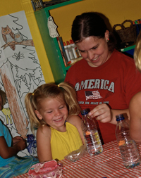 A young woman with a girl at a table with a red and white plaid tablecloth and plastic water bottles, holding a bottle by the top.