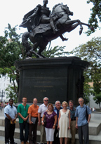 A group of people standing together in front of a large dark grey statue of a man on a horse, standing on two legs.