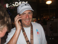 A man in a white shirt and white cap, speaking on a telephone.