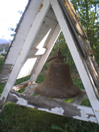 A large, rusted bell under a wooden triangle awning.