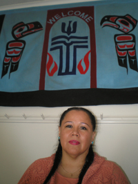 A woman beneath a large white banner with Tlingit and Presbyterian symbols.