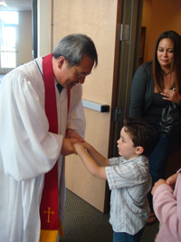 Jason Ku, in vestments, greets a boy.