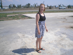 A woman stands on an empty lot where her church used to stand.