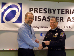Presbyterian Disaster Assistance Coordinator Randy Ackley receives a  check and shakes the hand of The Rev. Tom Dillard, both in front of a  Presbyterian Disaster Assistance banner.